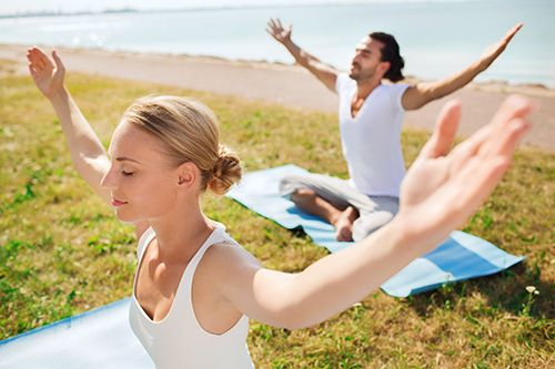 Couple Relaxing While Doing Yoga on the Beach
